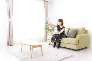 自宅でテレビを見る女性の写真素材 [FYI04705732]