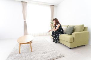 自宅でテレビを見る女性の写真素材 [FYI04705742]
