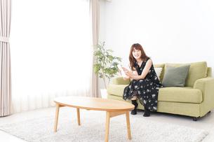 自宅でテレビを見る女性の写真素材 [FYI04705744]