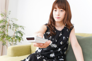 自宅でテレビを見る女性の写真素材 [FYI04705746]