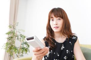 自宅でテレビを見る女性の写真素材 [FYI04705748]