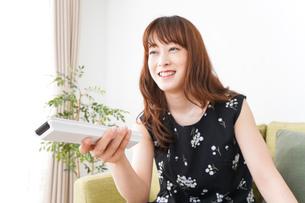 自宅でテレビを見る女性の写真素材 [FYI04705754]