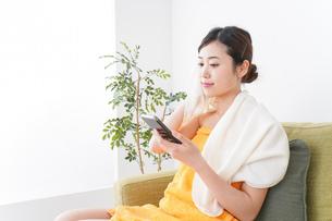 お風呂上がりにスマホをいじる女性の写真素材 [FYI04706241]