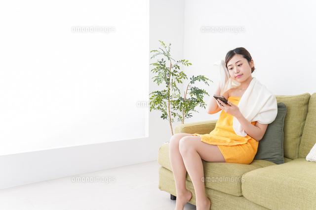 お風呂上がりにスマホをいじる女性の写真素材 [FYI04706251]