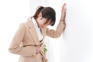 腹痛で苦しむビジネスウーマンの写真素材 [FYI04706902]