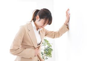 腹痛で苦しむビジネスウーマンの写真素材 [FYI04706906]
