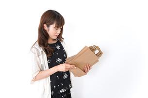 買い物袋を整理する店舗スタッフの写真素材 [FYI04707165]