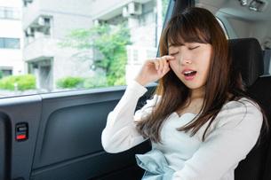 後部座席で寝る女性の写真素材 [FYI04707485]