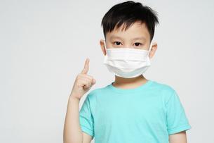 手でナンバーワンのサインをしているフェイスマスク姿の男の子の少年の写真素材 [FYI04708310]