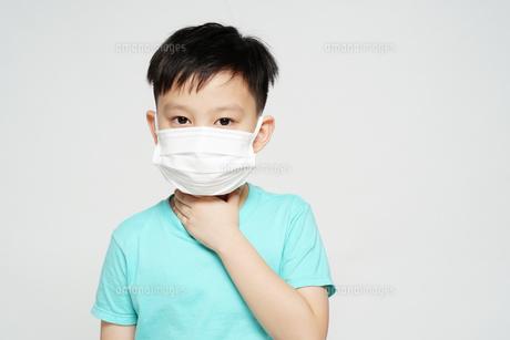 のどの痛みを訴えるフェイスマスク姿の男の子の写真素材 [FYI04708311]