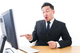 パソコンの前で憤慨するビジネスマンの写真素材 [FYI04708351]