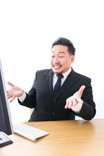 パソコンの前で憤慨するビジネスマンの写真素材 [FYI04708352]