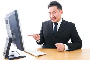 パソコンの前で憤慨するビジネスマンの写真素材 [FYI04708353]