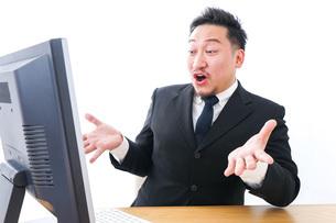 パソコンの前で憤慨するビジネスマンの写真素材 [FYI04708355]