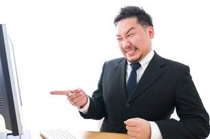 パソコンの前で憤慨するビジネスマンの写真素材 [FYI04708357]