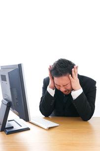 パソコンの前で憤慨するビジネスマンの写真素材 [FYI04708363]