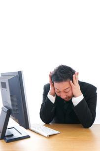 パソコンの前で憤慨するビジネスマンの写真素材 [FYI04708367]
