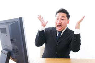 パソコンの前で憤慨するビジネスマンの写真素材 [FYI04708369]