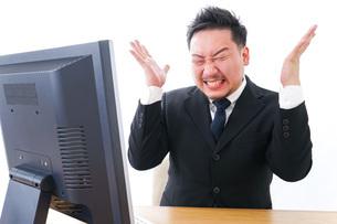 パソコンの前で憤慨するビジネスマンの写真素材 [FYI04708370]