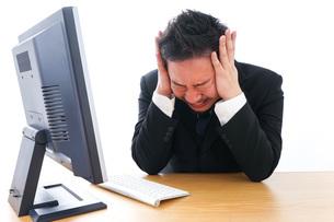 パソコンの前で憤慨するビジネスマンの写真素材 [FYI04708371]