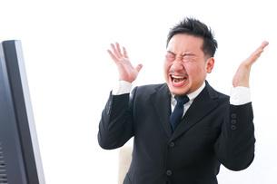 パソコンの前で憤慨するビジネスマンの写真素材 [FYI04708372]