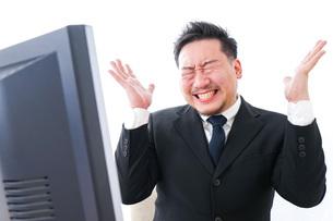 パソコンの前で憤慨するビジネスマンの写真素材 [FYI04708373]