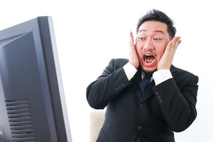 パソコンの前で憤慨するビジネスマンの写真素材 [FYI04708376]