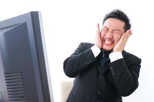 パソコンの前で憤慨するビジネスマンの写真素材 [FYI04708379]
