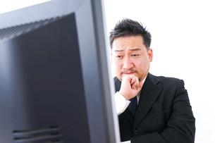 パソコンの前で憤慨するビジネスマンの写真素材 [FYI04708381]