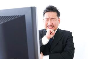 パソコンの前で憤慨するビジネスマンの写真素材 [FYI04708383]