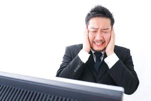 パソコンの前で憤慨するビジネスマンの写真素材 [FYI04708388]