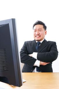 パソコンの前で憤慨するビジネスマンの写真素材 [FYI04708392]