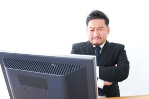 パソコンの前で憤慨するビジネスマンの写真素材 [FYI04708394]