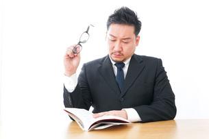 疲れて読書をするビジネスマンの写真素材 [FYI04708549]