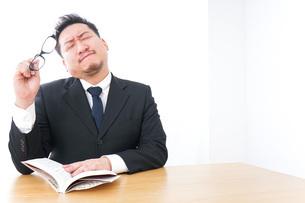 疲れて読書をするビジネスマンの写真素材 [FYI04708555]