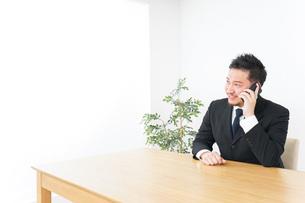 オフィスで電話をするビジネスマンの写真素材 [FYI04708759]