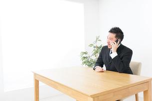 オフィスで電話をするビジネスマンの写真素材 [FYI04708771]