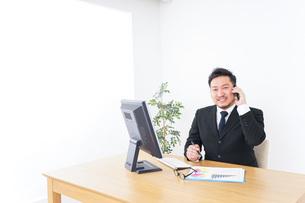 オフィスで電話をするビジネスマンの写真素材 [FYI04708778]