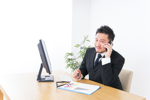 オフィスで電話をするビジネスマンの写真素材 [FYI04708783]