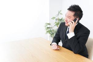 オフィスで電話をするビジネスマンの写真素材 [FYI04708786]