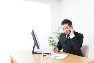 オフィスで電話をするビジネスマンの写真素材 [FYI04708790]