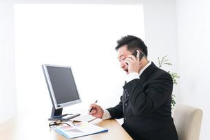 オフィスで電話をするビジネスマンの写真素材 [FYI04708794]