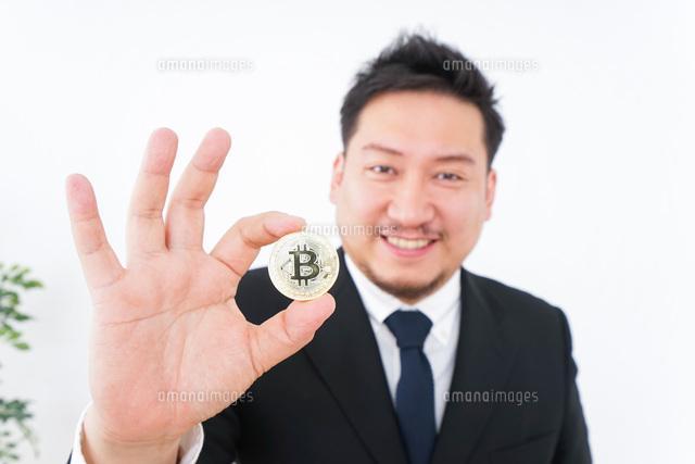 仮想通貨・ビットコインで稼ぐ男性の写真素材 [FYI04708808]
