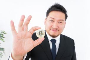 仮想通貨・ビットコインで稼ぐ男性の写真素材 [FYI04708810]