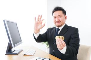 仮想通貨・ビットコインで稼ぐ男性の写真素材 [FYI04708811]