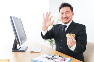 仮想通貨・ビットコインで稼ぐ男性の写真素材 [FYI04708812]