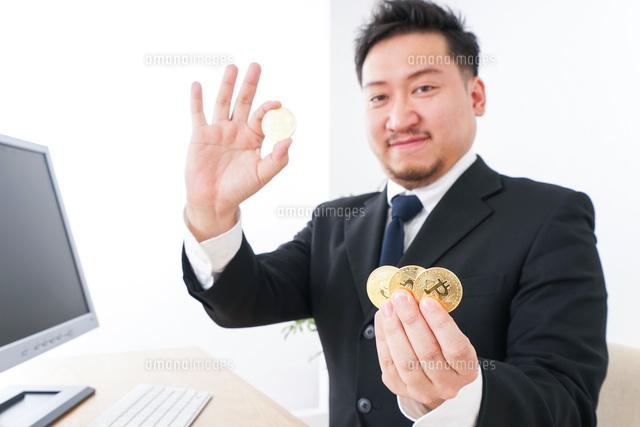 仮想通貨・ビットコインで稼ぐ男性の写真素材 [FYI04708814]