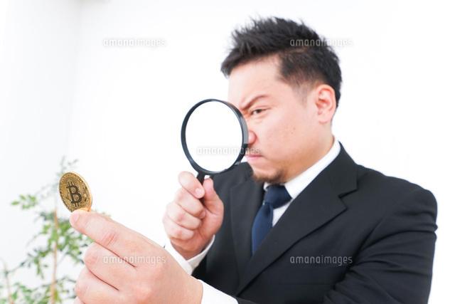 仮想通貨を調べるビジネスマンの写真素材 [FYI04708827]