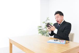 財布を見て驚くビジネスマンの写真素材 [FYI04708841]