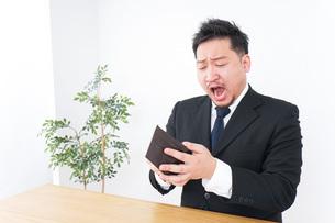 財布を見て驚くビジネスマンの写真素材 [FYI04708844]